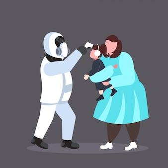 Человек в костюме хазмат, проверяющий температуру дочери с матерью, распространяющей эпидемию коронавируса