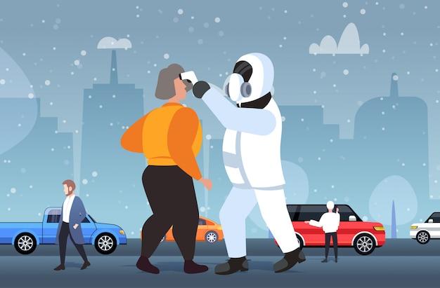 危険なスーツを着た男が屋外を歩いて病気の女性の温度をチェック