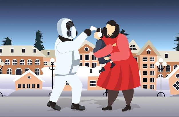 母と娘の屋外のコロナウイルス感染症の流行をチェックする防護服の男