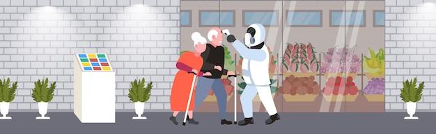 街の通りを歩いている年配の男性女性の温度をチェックする防護服の専門家