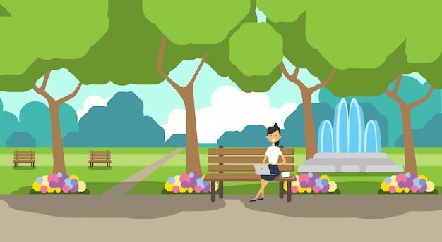 Городской парк предпринимательница держит ноутбук сидит деревянная скамейка зеленый газон цветы фонтан деревья городской пейзаж шаблон фон горизонтальный плоский