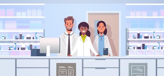 ミックスレース医師薬剤師チーム薬局のカウンターに立っている現代のドラッグストアインテリア医学医療概念水平肖像
