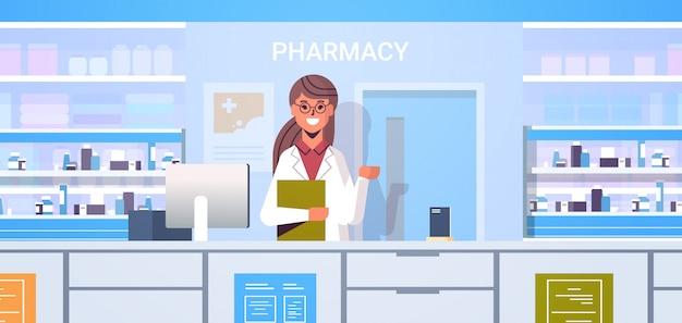 薬局のカウンターで現代のドラッグストアインテリア医学ヘルスケアの概念の水平方向の肖像画に立っているクリップボードと女性医師薬剤師