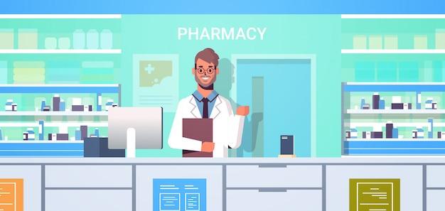 薬局のカウンターで現代のドラッグストアインテリア医学ヘルスケアの概念の水平方向の肖像画に立っているクリップボードと男性医師薬剤師