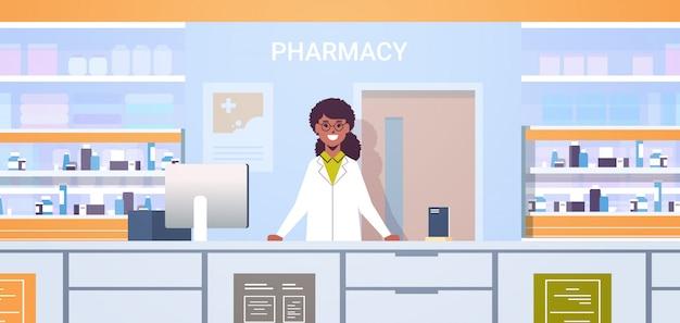 アフリカ系アメリカ人の女性医師薬剤師が薬局のカウンターに立っている現代のドラッグストアインテリア医学ヘルスケアの概念の水平方向の肖像画