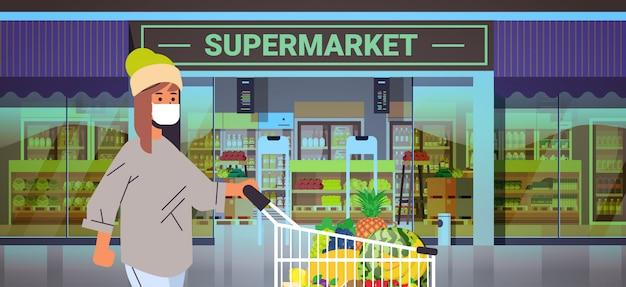 トロリーカート検疫コロナウイルスの流行の概念の人々が食料品店のスーパーマーケットの外観の肖像画の水平方向で商品を購入する医療防護マスクの女性客