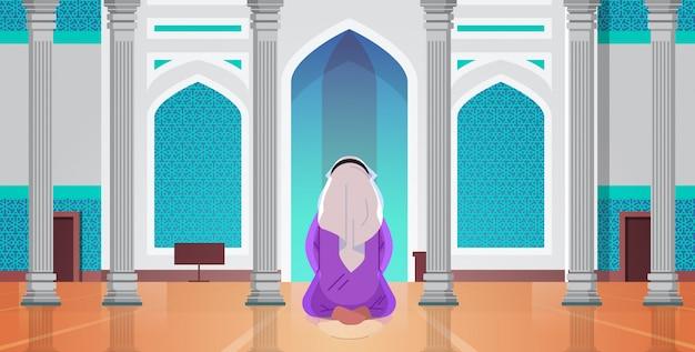 宗教的なイスラム教徒の男性がひざまずいて、モスクの建物ラマダンカリーム聖なる月の宗教概念背面図全長水平の内部で祈って