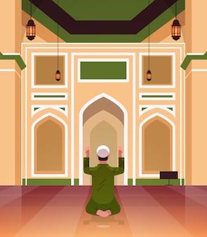 イスラム教徒のイスラム教徒の男がひざまずいて、モスクの建物ラマダンカリームの聖なる月の宗教概念背面ビュー全長垂直の内側に祈る