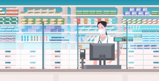 Женщина-врач фармацевт в маске стоит в аптеке счетчик аптека интерьер