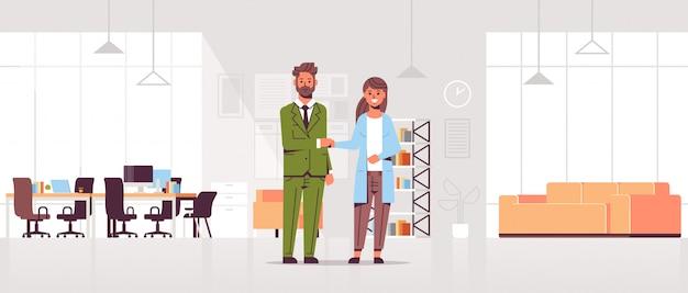 Бизнесмены мужчина женщина рукопожатие деловые партнеры пара рукопожатие во время встречи соглашение партнерство современный центр совместной работы офис интерьер