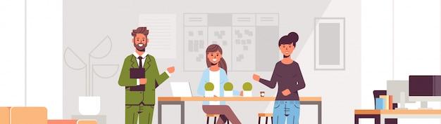 Пара коллег, указывая на новую работницу, представляя наемного работника в коллектив современный интерьер центра совместной работы офиса