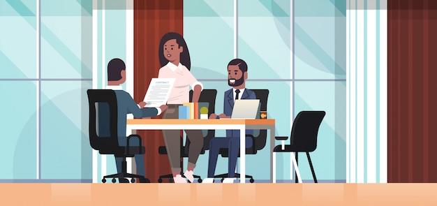 Предприниматели обсуждая контракт во время встречи развития бизнеса коллеги работая с со-инвестиционным документом концепция переговоров интерьер офиса горизонтальный