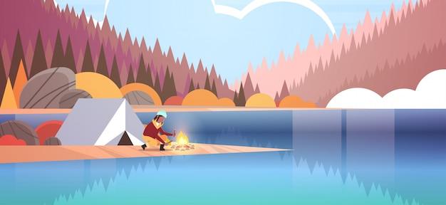 たき火ハイキングキャンプコンセプト秋の風景自然川森山背景水平のための薪を保持しているテントキャンプの女の子の近くに火を作る女性ハイカー