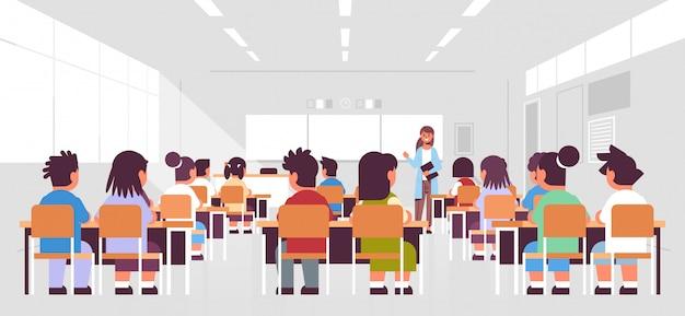 生徒グループが座っていると教室で女教師に耳を傾けて授業教育概念現代クラスの部屋のインテリアを教える