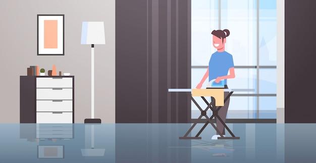 Домохозяйка гладит одежду молодая женщина держит утюг улыбается девушка делает по дому концепт современный квартира интерьер женщина мультипликационный персонаж