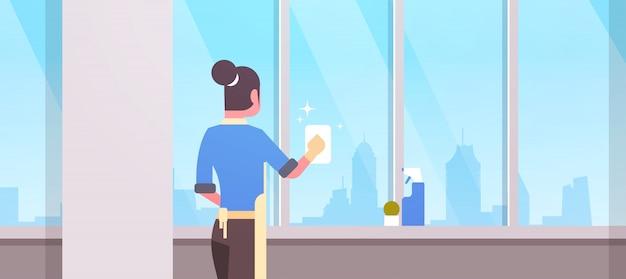 Женщина в перчатках и фартуке, мытье окон тряпкой, очиститель спрей, вид сзади, домохозяйка, делающая работу по дому, концепция современной гостиной, интерьер, портрет.