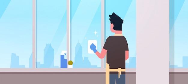 Человек в перчатках и фартук, мытье окон с помощью тряпки, чище, спрей, вид сзади, парень, работа по дому, концепция, современная квартира, интерьер гостиной