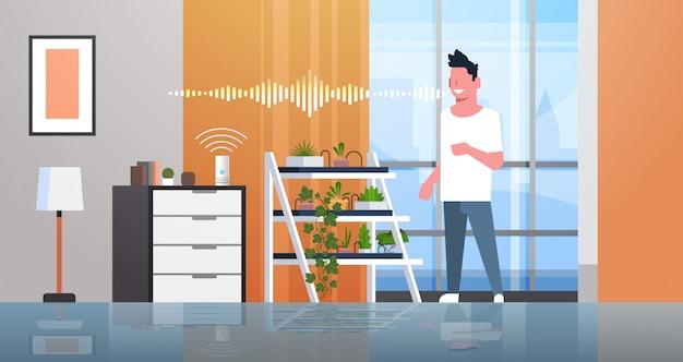 Человек, использующий интеллектуальный динамик, распознавание голоса, активирован, цифровые помощники, концепция, автоматическая система полива, современная гостиная, интерьер, квартира, горизонтальный, полная длина
