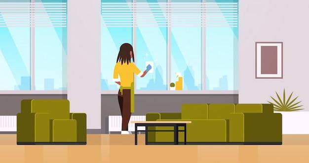 Женщина в перчатках и фартуке, мытье окон тряпкой, очиститель спрей, вид сзади, домохозяйка, делающая работу по дому, концепция современной гостиной, интерьер, горизонтальный, полная длина