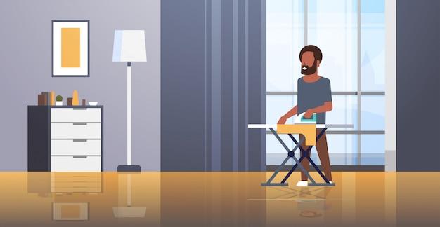 Человек гладит одежду парень держит утюг делает домашнее хозяйство уборка концепция современный дом гостиная интерьер мужской мультипликационный персонаж полная длина горизонтальный