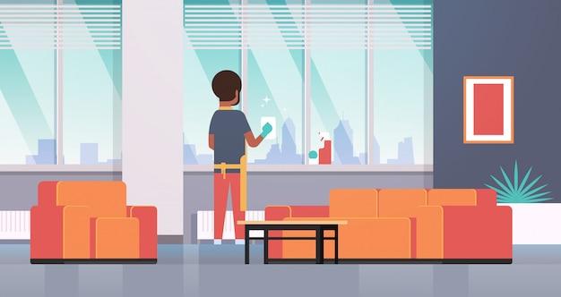 Человек в перчатках и фартуке, мытье окон тряпкой, спрей, вид сзади, парень, работающий по дому, концепция, современная квартира, гостиная, интерьер, полная длина, горизонтальный