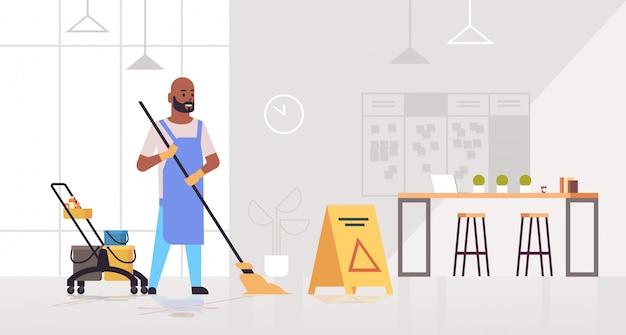 男の制服クリーニングサービスコンセプト管理人で床を掃除する男性清掃用品供給トロリーカート近くの創造的な共同作業センターオフィスインテリア全長水平