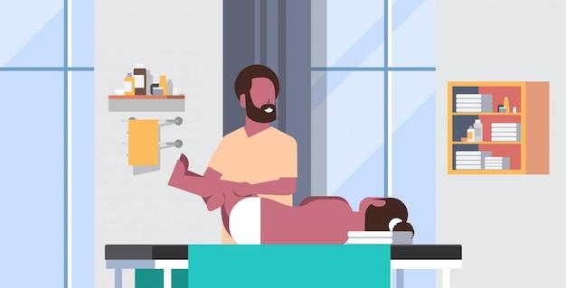 マッサージテーブルに横たわっている女の子マッサージセラピストヒーリング治療を行うマッサージ患者治療脚手動の理学療法の概念医療クリニックキャビネットインテリア水平