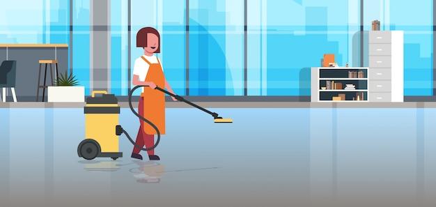 制服掃除サービス床ケアモダンな共同作業オフィスインテリアでプロの掃除機女性クリーナー用務員を保持している女性