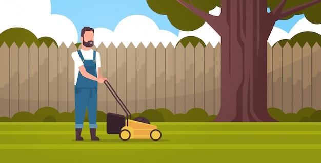 男庭師が芝生の発動機と緑の草を刈る農家移動庭裏庭ガーデニング