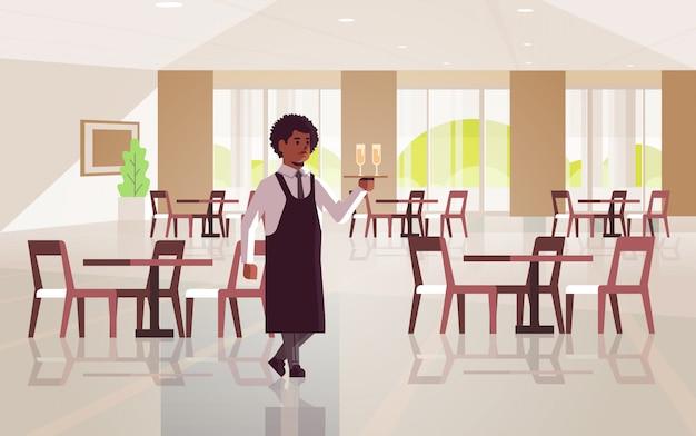 Профессиональный официант держит поднос с двумя бокалами шампанского