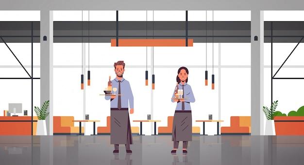 Пара официантов, держащая бутылки и бокалы с шампанским и вином на подносе