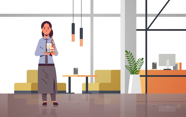 Профессиональная официантка, держащая бутылку и бокалы с шампанским на подносе