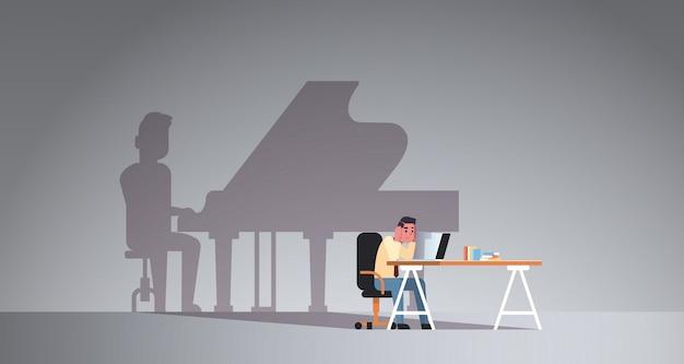 Перегруженный человек сидит на рабочем месте, используя ноутбук