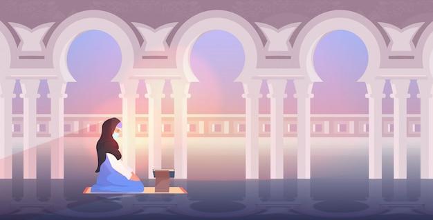 ラマダンカリームの聖なる月の宗教概念の中に読書コーランを祈って宗教的なイスラム教徒の女性