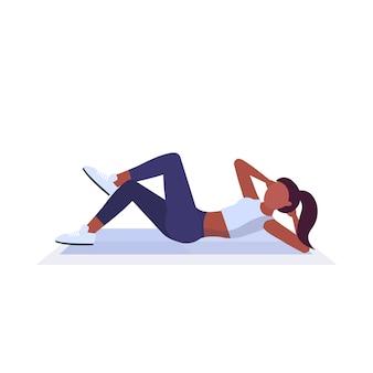 ジムの有酸素運動の健康的なライフスタイルのコンセプトホワイトバックグラウンドでトレーニングマットの女の子にプレス演習を行うスポーツ女性