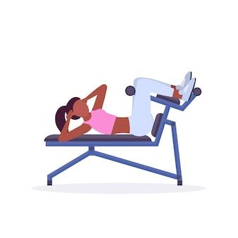 ジムのワークアウト健康的なライフスタイルコンセプトホワイトバックグラウンドでトレーニングのベンチの女の子にプレス腹部の演習を行うスポーツ女性