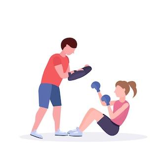 Спортсменка боксер делает упражнения с личным тренером девушка боец в синих перчатках работает на полу бой клуб концепции здорового образа жизни белый фон