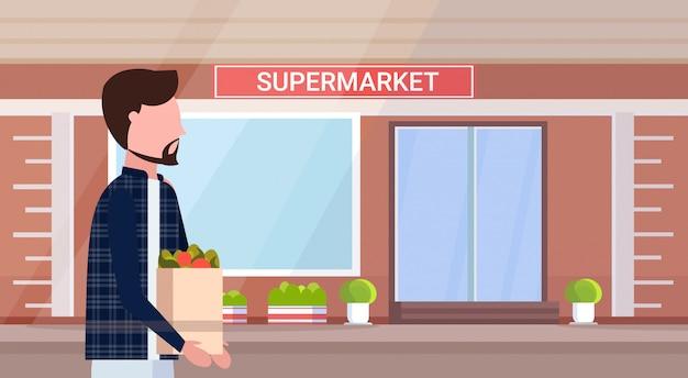 食料品の男性の漫画のキャラクターが屋外のモダンな食料品店のスーパーマーケットの外観の水平方向の肖像画を歩いて買い物袋を運ぶ男