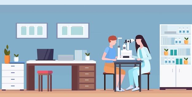 女性の眼科医が眼科手術を行う男性の患者の視力医師をチェック