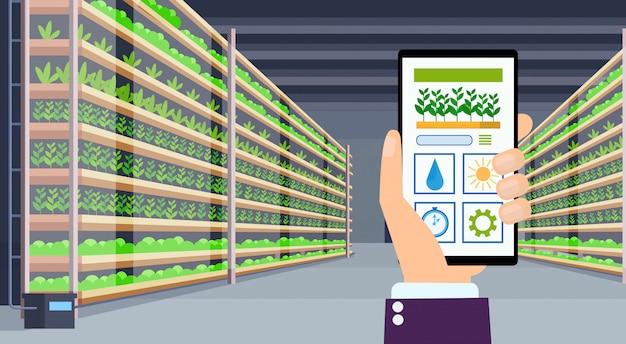モバイルアプリを使用して手スマートコントロール農業システム農業コンセプトスマートフォン画面現代の有機水耕垂直ファームインテリア緑の植物成長産業水平