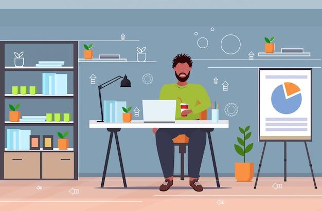 ノートパソコンの不健康な栄養肥満コンセプトモダンなオフィスインテリアフラット全長水平で職場の机に座ってコーラ太りすぎの男を飲むビジネスマン