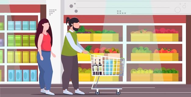 食料品とトロリーカートを押してカップル肥満男性女性一緒に買い物肥満不健康なライフスタイルコンセプトモダンな食料品店のインテリアフルレングスフラット水平