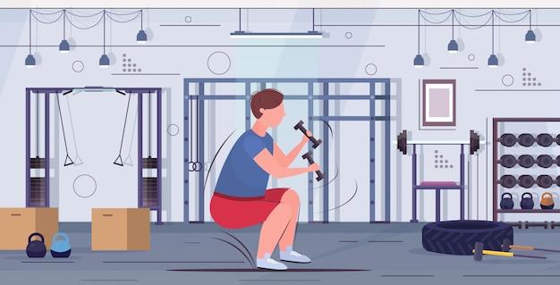 Человек делать приседания упражнения с гантелями избыточный вес парень тренировки тренировки потеря веса концепция современный тренажерный зал интерьер плоский полная длина горизонтальный