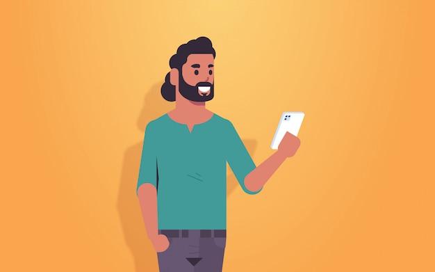 Мужчина держит мобильный телефон арабский парень с помощью смартфона мобильное приложение социальные медиа коммуникация концепция мужской мультфильм характер портрет горизонтальный