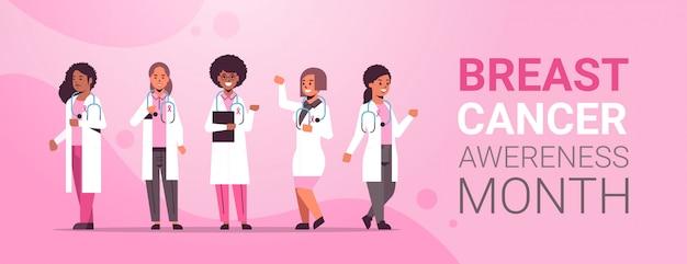 ピンクのリボンとコートを着ている乳がんの日医師ミックスレース病院の同僚チーム立って一緒に病気の意識と予防の概念フラット全長コピースペース水平