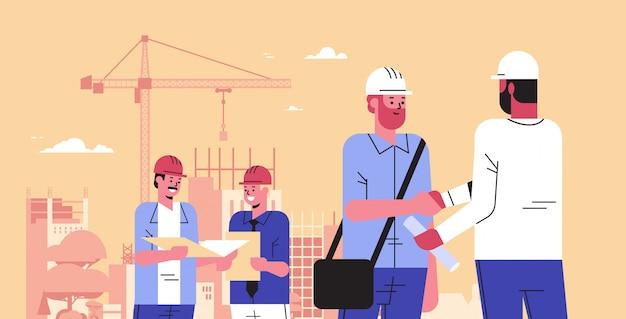 ビルダーのチームが会議中に握手ミックスエンジニアヘルメット労働者のヘルメットの青写真のハンドシェイク契約概念建設サイトの背景の肖像画の水平方向の新しいプロジェクトを議論