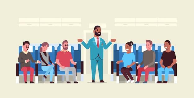 非常口を示す制服を着たアフリカ系アメリカ人の客室乗務員のミックスレースの乗客のための指示を説明するスチュワード非常口安全デモコンセプト飛行機ボードインテリア水平