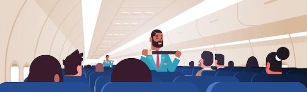 スチュワードが乗客に、緊急時のシートベルトファスニングの使用方法を説明します。