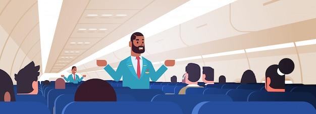 非常口を示す制服を着た乗客のアフリカ系アメリカ人男性の客室乗務員のための指示を説明するスチュワードの出口の安全デモのコンセプト飛行機のボードのインテリア水平