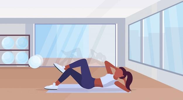 ジムのエアロビクストレーニング健康的なライフスタイルコンセプトフラットな近代的なヘルスクラブスタジオインテリア水平でトレーニングマットアフリカ系アメリカ人の女の子にプレス演習を行うスポーツ女性